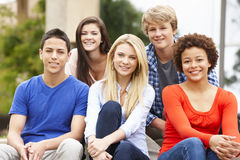 Multi racial student group sitting outdoors Stock Photo