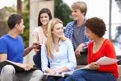 Multi racial student group sitting outdoors Stock Photos