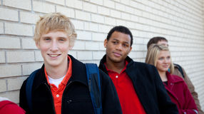 Multi-racial Studenten gegen eine Backsteinmauer Stockbilder