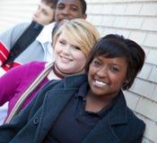Multi-racial studenten tegen een bakstenen muur Royalty-vrije Stock Foto