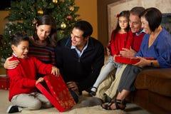 Multi regali di Natale di apertura della famiglia della generazione Fotografie Stock