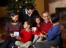 Multi regali di Natale di apertura della famiglia della generazione Immagine Stock