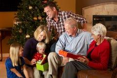Multi regali di Natale di apertura della famiglia della generazione Fotografia Stock