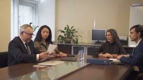 Multi sócios comerciais étnicos em negociações na sala de reuniões do escritório filme