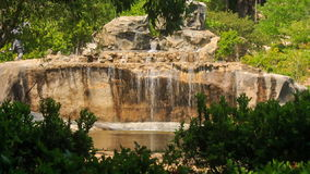 Multi-stage waterfall into stone lake in tropical tourist park stock video