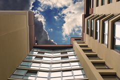 Multi-storey building on the background of the sky with clouds. Photo from below stock photo