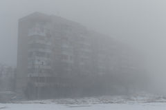 Multi-storey building in the fog. Foggy morning in the winter. Foggy morning. Multi-storey building in the fog. Snowy morning and fog Stock Photo