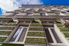 multi-storey building of green color with a textured facade stock photos
