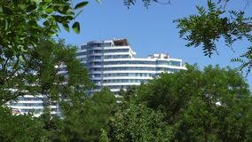 Multi-storey building in the green tree branches. Against the background of the blue sky stock footage