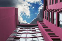 Multi-storey building of purple in the background of the sky with clouds. Photo from below stock photo
