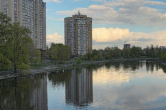 Multi-storey building is reflected in the water. Quiet and cozy area on the left side of the Dnieper River in Kiev Stock Images