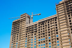 Multi-storey building under construction. On the background of blue sky windows, production Stock Photos