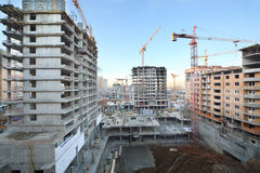Multi-storey buildings under construction and cranes Stock Photos