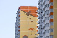 A multi-storey house with a painted wall. Figure depicting the landing of paratroopers from an airplane stock images