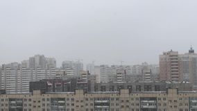 Multi-storey houses during a snowfall in winter in cloudy weather stock video footage