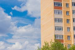 Multi-storey residential building on blue sky and clouds background. Multi-storey residential building on blue sky and Cumulus clouds background summer white stock photos