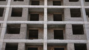Multi-storey residential building under construction. Closeup view, camera moving up. Multi-storey residential building under construction. Closeup view, camera stock footage