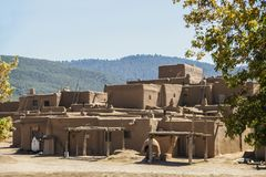 Multi-storied adobe mud Native American pueblo dwelling in the Southwestern United states with drying racks and outside ovens with. Mountains in the distance stock photography