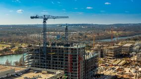 Multi storied building under construction with mechanic cranes in 4k time lapse. Multi storied building under construction with mechanic cranes in time lapse stock footage