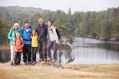 Multi supporto della famiglia della generazione che abbraccia da un lago, sorridente alla macchina fotografica, vista frontale, d immagine stock