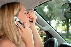 Multi-tasking. Applying makeup and talking on cell phone in car Stock Image