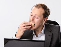Multi tasking businessman eats and works. Busy hardworking business man eats lunch at his desk while working Royalty Free Stock Photo