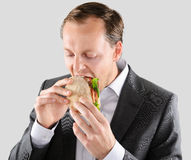 Multi tasking businessman eats and works. Busy hardworking business man eats lunch at his desk while working Stock Images