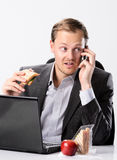Multi tasking businessman eats and works Stock Images
