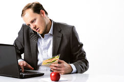 Multi tasking businessman works through lunch Royalty Free Stock Image