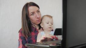 Multi-tasking, freelance en moederschapconcept - de werkende jongen van de moederbaby en laptop computer thuis Familie, moeder stock footage