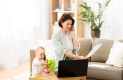 Working mother with baby calling on smartphone. Multi-tasking, freelance and motherhood concept - working mother with papers calling on smartphone and baby son royalty free stock photo