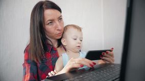 Multi-tasking, frilans- och moderskapbegrepp - arbetande mamman behandla som ett barn pojken och bärbar datordatoren hemma Familj lager videofilmer