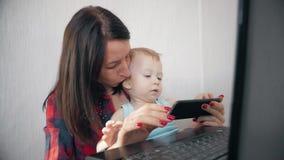 Multi-tasking, frilans- och moderskapbegrepp - arbetande mamman behandla som ett barn pojken och bärbar datordatoren hemma Familj arkivfilmer