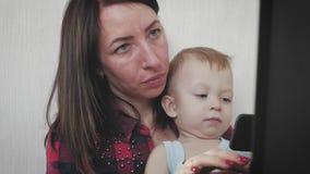 Multi-tasking, frilans- och moderskapbegrepp - arbetande mamman behandla som ett barn pojken och bärbar datordatoren hemma Familj stock video