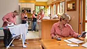 Multi-tasking Household Chores. Middle aged average woman performing daily household chores and tasks simultaneously as if cloned Stock Photography