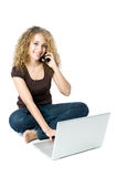 Multi-tasking on the phone and computer. A beautiful young women on a laptop computer and mobile phone Royalty Free Stock Photo