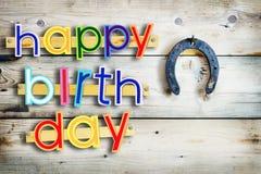 Multi testo dipinto colorato luminoso di buon compleanno sul legno con un ferro di cavallo Fotografie Stock Libere da Diritti