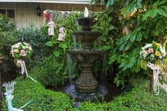 multi-tiered fontein en bloemboeket in tuin Royalty-vrije Stock Afbeelding