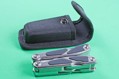 Multi tool. Folded multi tool with case on a green background Royalty Free Stock Photos