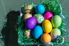 Multi uova di Pasqua colorate in erba di plastica verde Fotografie Stock