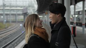 The multiathnical couple is hugging and enjoying the meeting in the railway station. The young korean man in black coat is tlking to his european girlfriend stock video footage
