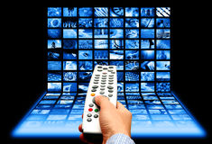 Multichannel choice. Male hand holding a remote in front of multi screens Royalty Free Stock Image