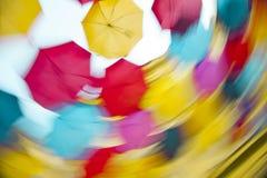 Multiclored que mueve el fondo borroso de los paraguas Imagen de archivo