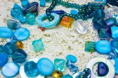 Multicolor стеклянные бусины граница, край с местом для текста Славные голубые, синие и желтые шарики на предпосылке вязания крюч стоковая фотография