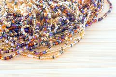 Multicolor beads. Nice, brown, dark yellow and beige beads on old wooden colored background. Place for text, copyspace. An old sty Royalty Free Stock Image