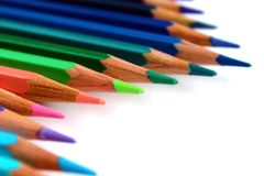 Bright color pencils diagonal wave on white background with green pencil on focus royalty free stock image