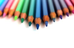 Bright color pencils horizontal wave on white background with blue central pencil on focus Royalty Free Stock Images