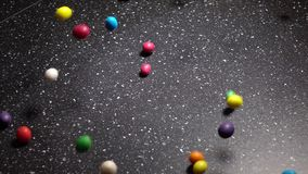 Multicolor Candy Falling Down on Black Table stock video