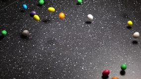 Multicolor Candy Falling Down on Black Table stock video footage
