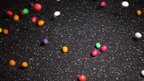 Multicolor Candy Falling Down on Black Table stock footage